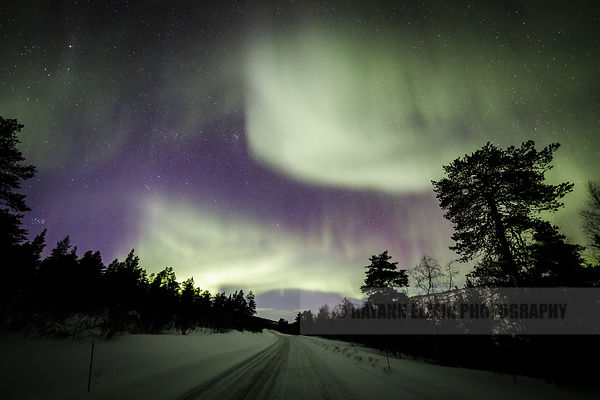 Northern lights above empty road in the far north of Lapland, Finland