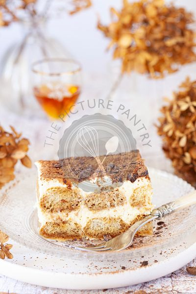 A slice of Italian tiramisu on a glass plate