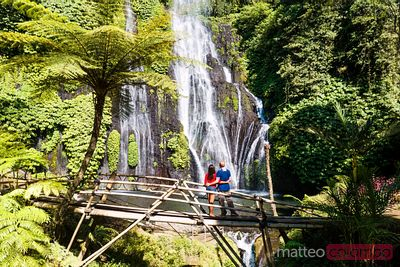 Tourist couple looking at waterfall, Munduk, Bali, Indonesia