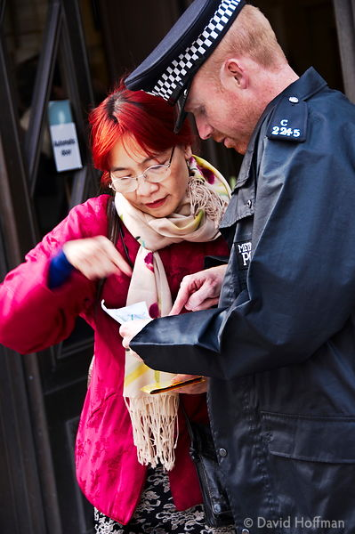 Police constable gives directions to a tourist in central London.