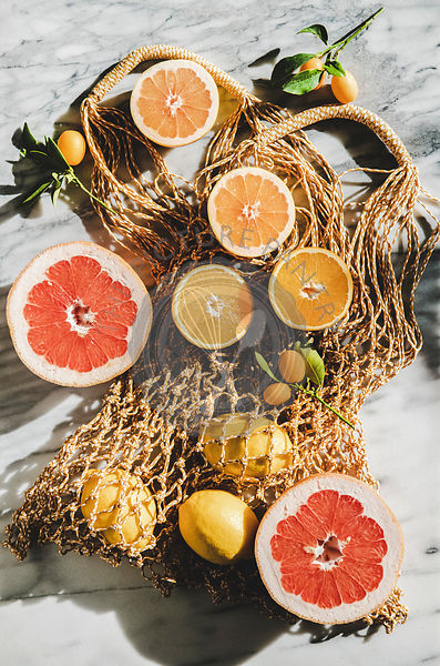 Flat-lay of summer net bag with fresh citrus fruits, close-up