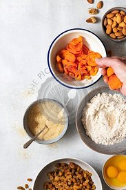 Wholemeal fruit cake ingredients with dried apricots being placed in a bowl.