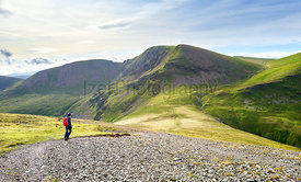 A hiker and their dog walking along a rocky path towards the summit of Sail and Crag Hill in the Lake District, England, UK.