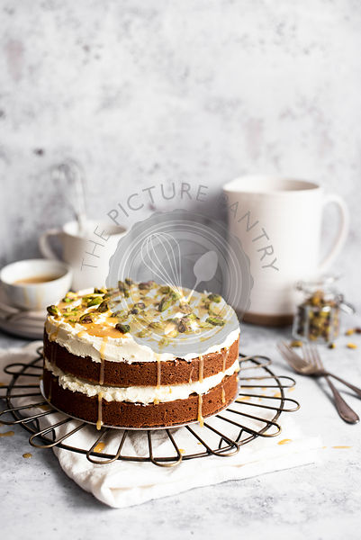 Chocolate Sandwich Cake With Vanilla Buttercream, Drizzled In Caramel And Sprinkled With Pistachios