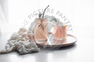 Pink grapefruit drink in two differently sized and patterned drinking glasses, garnished with rosemary and a metal straw on a...