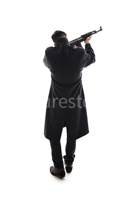 A semi-silhouette of a mystery man in a long black winter coat, aiming an AK-47– shot from eye level.