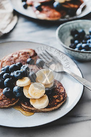 Banana pancakes with bluelerry and honey over marble table
