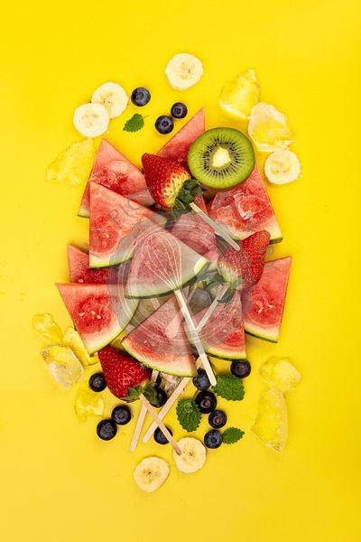 Slices of watermelon , fruits and berrieson yellow background