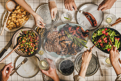Flat-lay of people having dinner with frilled meat and vegetables