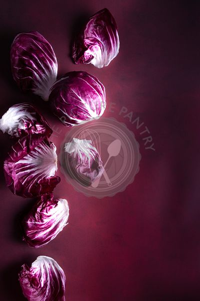 Moody Radicchio against a purple background with copy space
