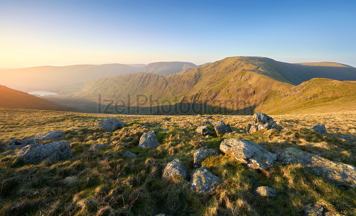 The warm morning glow of sunrise over the summit of High Street with Mardale Ill Bell and Harter Fell to the left from the su...