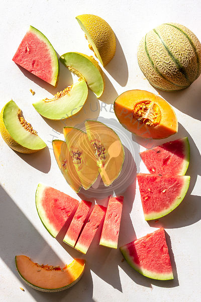 Slices of watermelon,cantaloupe and honeydew melon on the table,top view