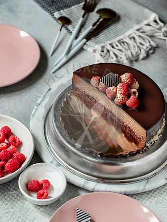 Chocolate truffle cake with raspberries and chocolate decoration on top