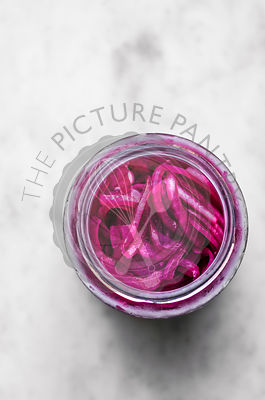 Pickled Red Onions in a jar on a marble surface