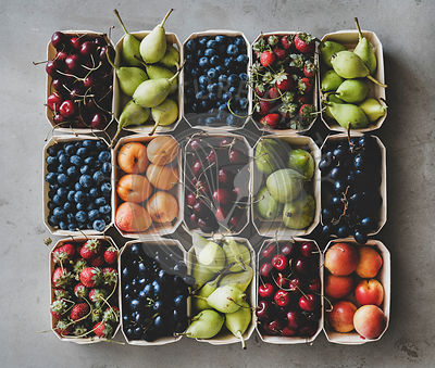 Summer fruit and berry assortment in wooden boxes
