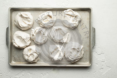 Meringues on a baking tray, on a white textured background.