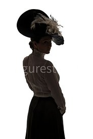 A Silhouette of an Edwardian woman in a big hat, standing and looking over her shoulder – shot from eye-level.