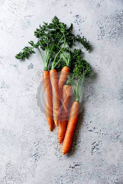 Fresh carrots on a textured blue background.