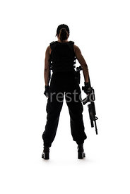 A silhouette of a tough woman, holding a rifle – shot from low level.