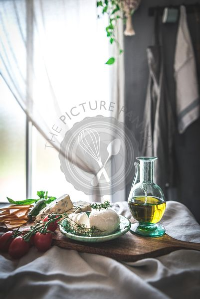 Mozzarella, tomatoes and olive oil next to a window in a rustic kitchen