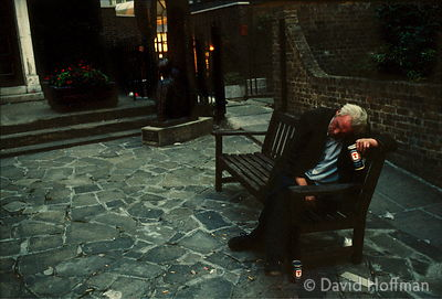Homeless alcoholic man on bench outside night shelter at St Botolph's crypt centre, Aldgate, London.