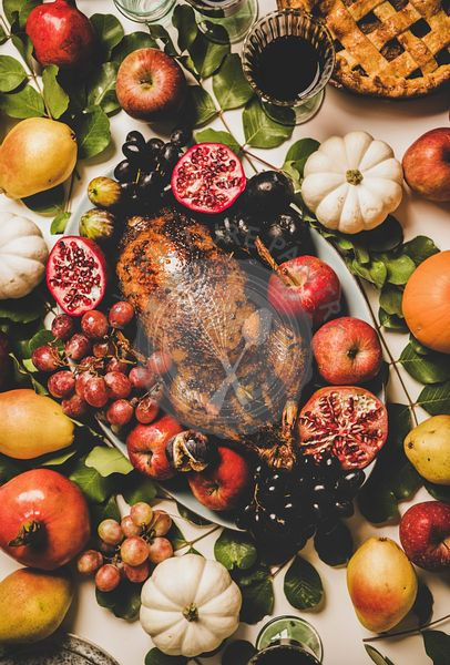 Thanksgiving dinner with roasted duck in fruits, vegetables and drinks