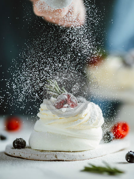 Woman sprinkles icing sugar on mini Pavlova cake with fresh berries