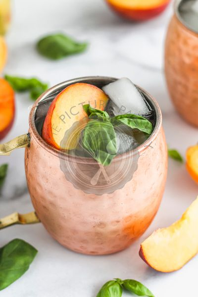 Moscow mule garnished with peach slice and basil leaves