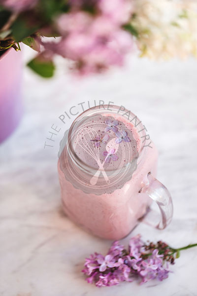Strawberry smoothie with lilac flowers