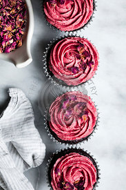 Decorating a chocolate muffin with pink frosting