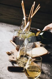 White wine pouring into glasses with charcuterie assortment on the stone background