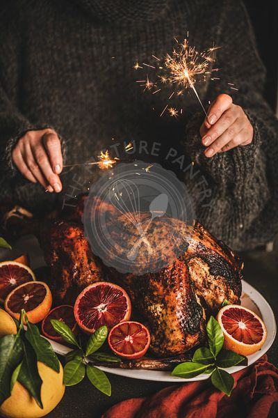 Woman in sweater burning sparkles over Christmas whole roasted turkey