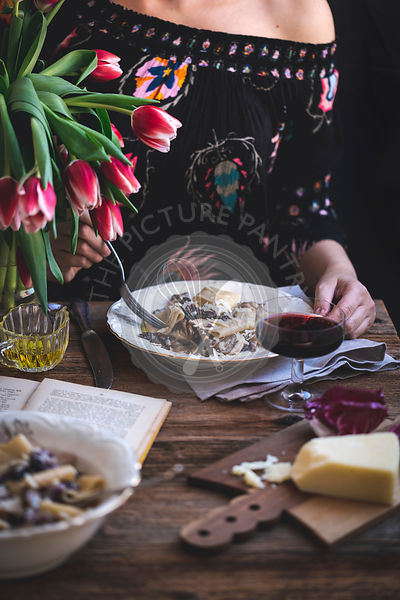 Woman eating pasta with radicchio, panceta and Parmesan