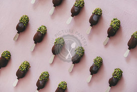 Chocolate glazed popsicle ice-cream with pistachio icing over pink background
