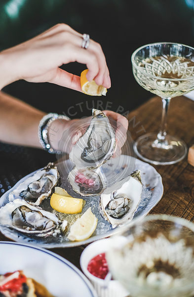 Woman squeezing lemon juice to oysters in plate with ice