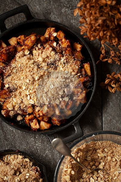Pear and Chocolate crumble being assembled in cast iron skillets ready for baking