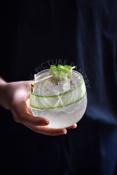 Cocktail with Cucumber in a womans hands