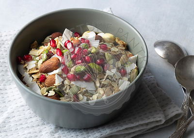Breakfast bowl filled with homemade muesli, almonds, dried coconut, pistachio nuts and pomegranate seeds.