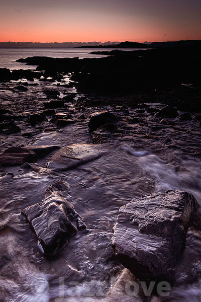 Sunset on scenic rocky beach on West coast of Scotland.