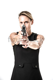 A blonde woman standing and pointing a gun – shot from eye level.
