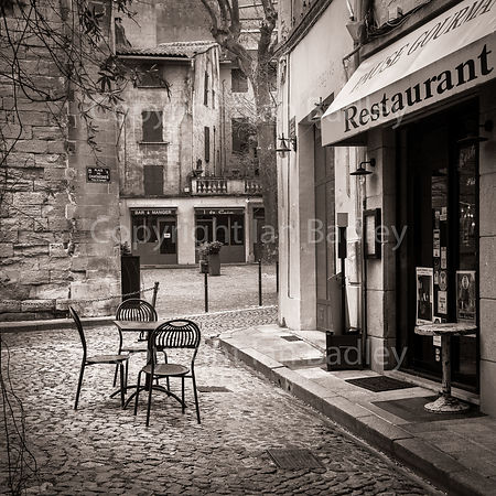 Empty cafe table  on cobbled street in France (Light sepia)