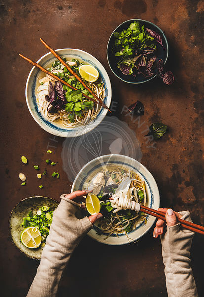 Womans hands with chopsticks and lime and vietnamese Pho-Ga soup