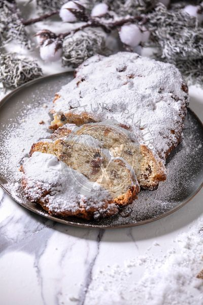 Christmas baking stollen cake with xmas decorations over white marble