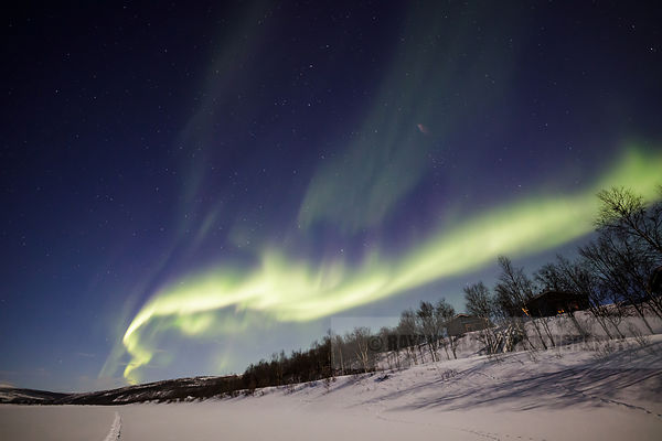 Aurora above cottage and the Tenojoki River in Utsjoki, Lapland, Finland