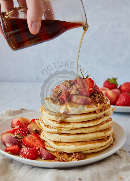 Pouring Maple Syrup Over A Stack of American Pancakes with Stawberries and Peaches