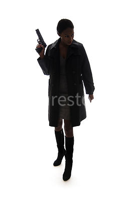 A tough woman, walking with a gun, in silhouette – shot from eye level.