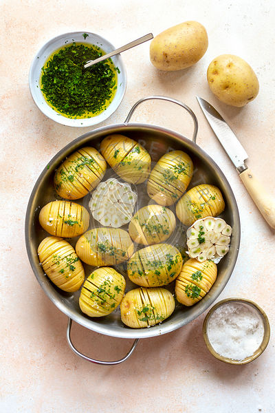 Preparing hasselback potaoes.Sliced potatoes drizzled with parsley dressing ready to bake.