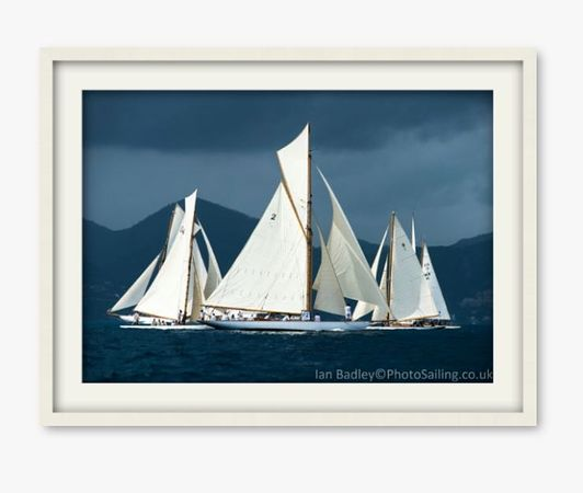 Classic yachts including 'Kelpie' wait for the start of racing with a storm brewing over the mountains near Cannes.