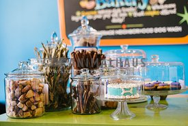 Treats, a cake, cupcakes and bully sticks  on display on the counter of a store