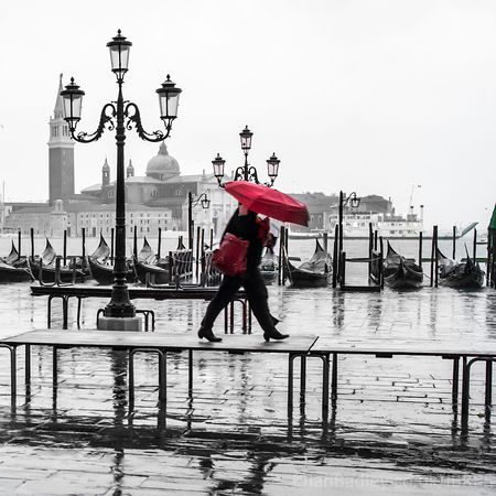 Red umbrella on the walkway in Venice
